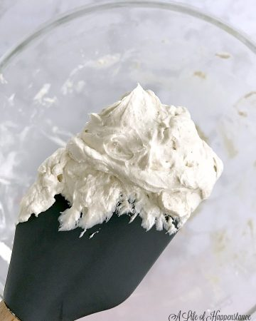 A grey spatula full of vanilla Italian meringue buttercream.