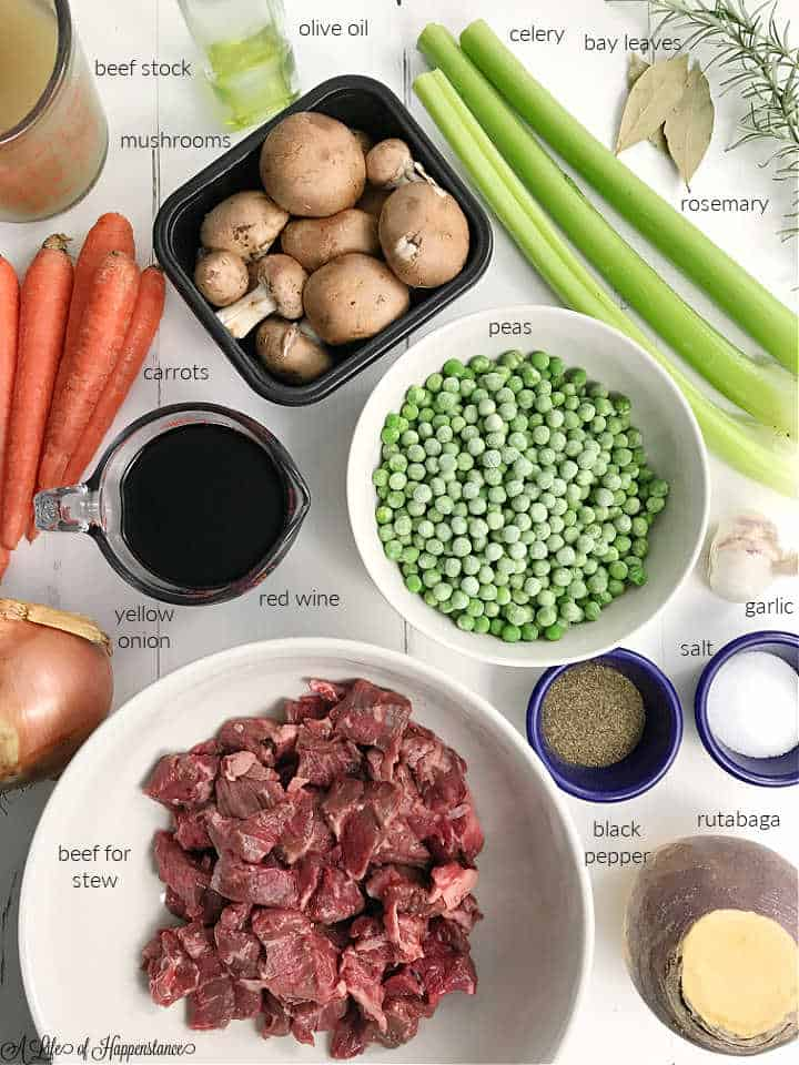 All the ingredients needed to make the stew; beef stock, olive oil, celery, bay leaves, mushrooms, rosemary, carrots, peas, yellow onion, red wine, garlic, beef for stew, black pepper, salt, rutabaga.
