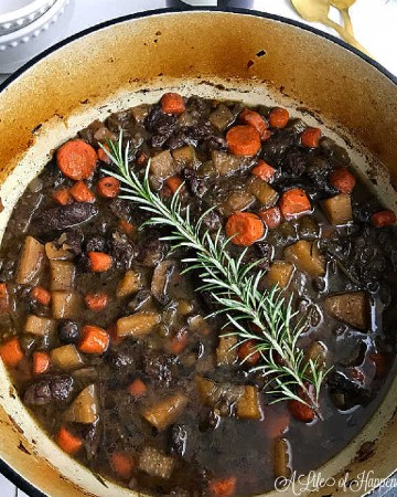 A large Dutch oven filled with homemade beef stew and garnished with a fresh sprig of rosemary.