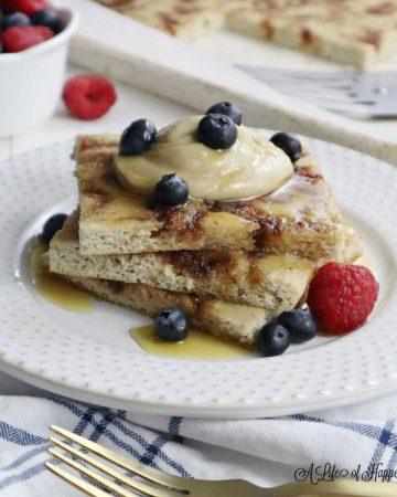 Three sheet pan pancakes on a white plate topped with cashew cream, honey, and berries.