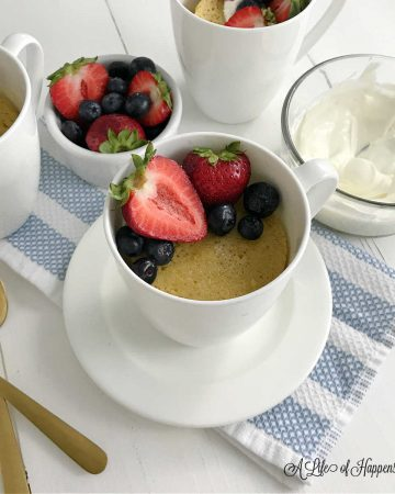 Vanilla mug cake in a white cup toped with fresh berries.