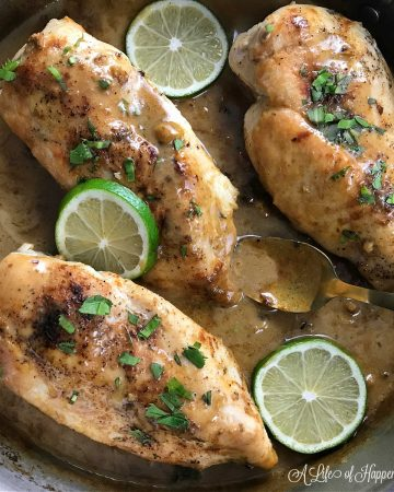 Three chicken breasts in a skillet with coconut lime sauce garnished with culantro and lime slices.