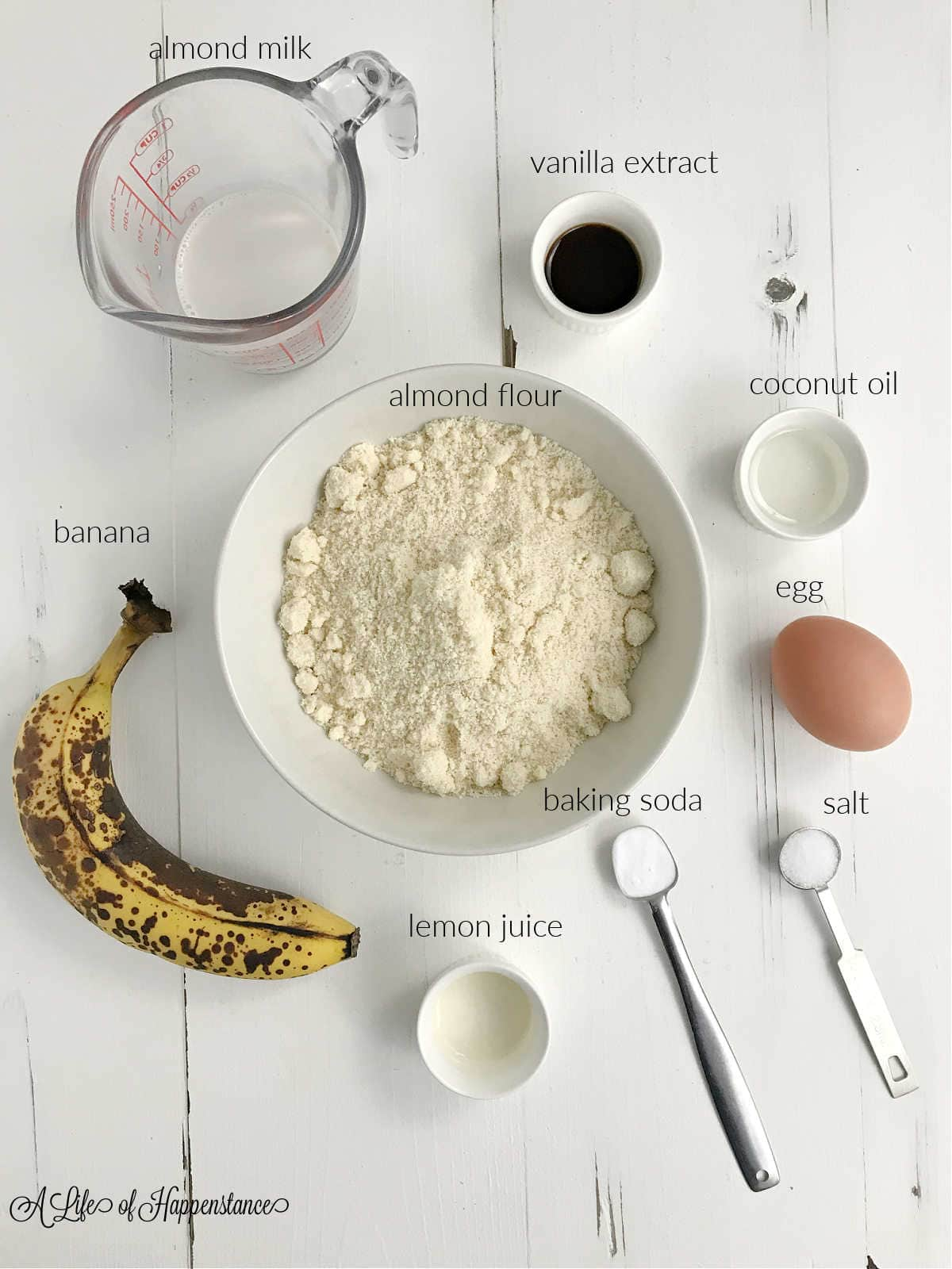 Ingredients for the smash cake; almond milk, vanilla extract, coconut oil, almond flour, banana, egg, lemon juice, baking soda, salt.