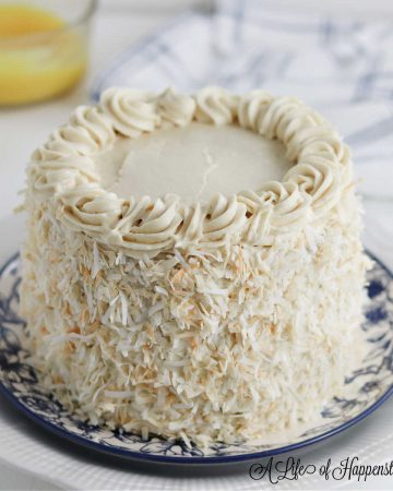 The decorated almond coconut cake on a white and blue flower plate.