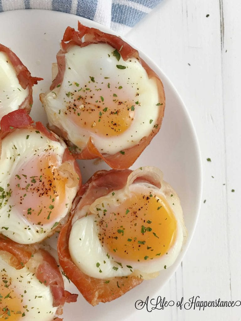 Prosciutto baked egg cups on a white plate.