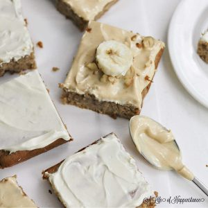 The cut frosted banana bars on a white table and spoonful of peanut butter frosting.