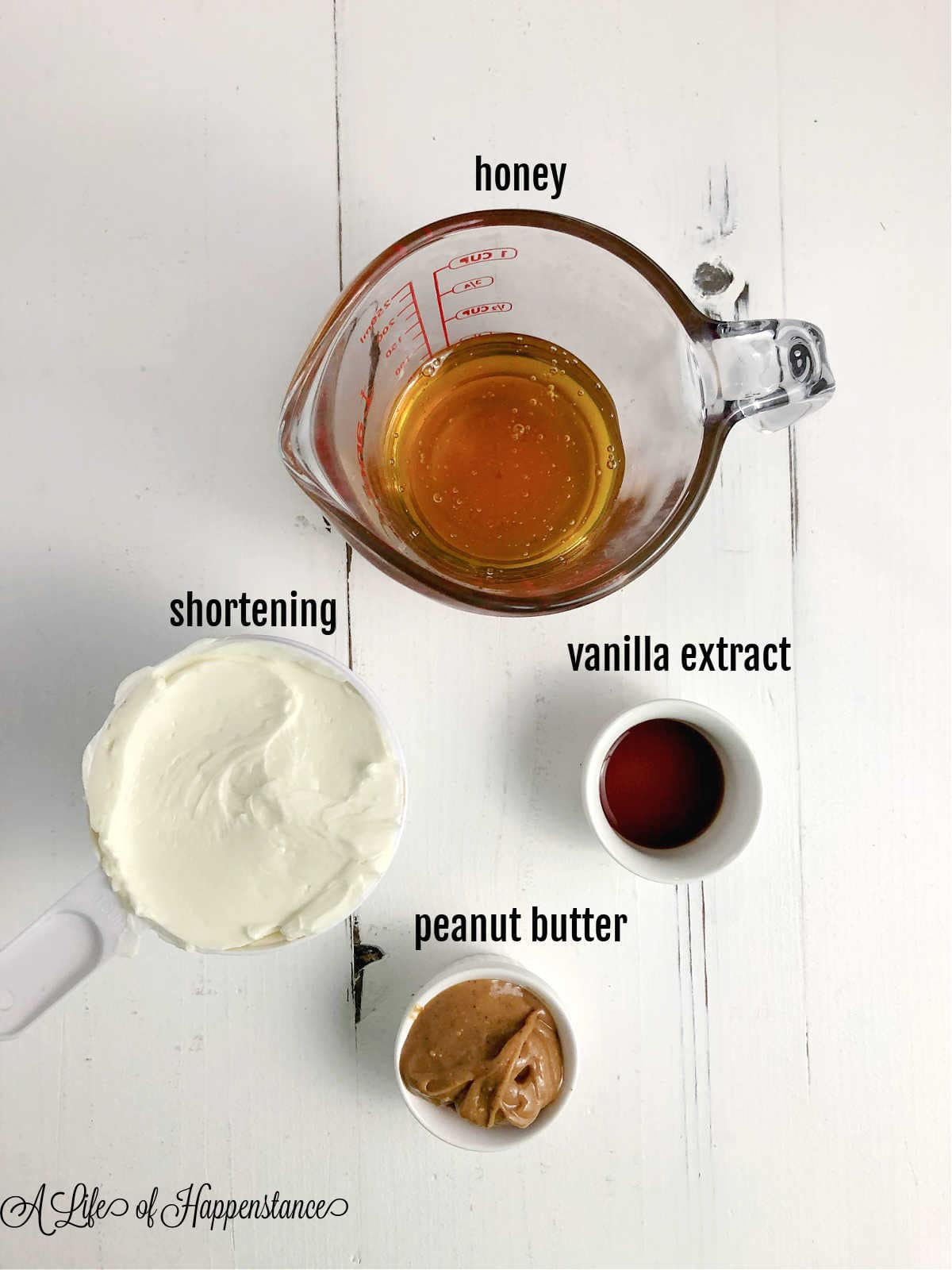 Ingredients for the frosting; honey, shortening, vanilla extract, and peanut butter.