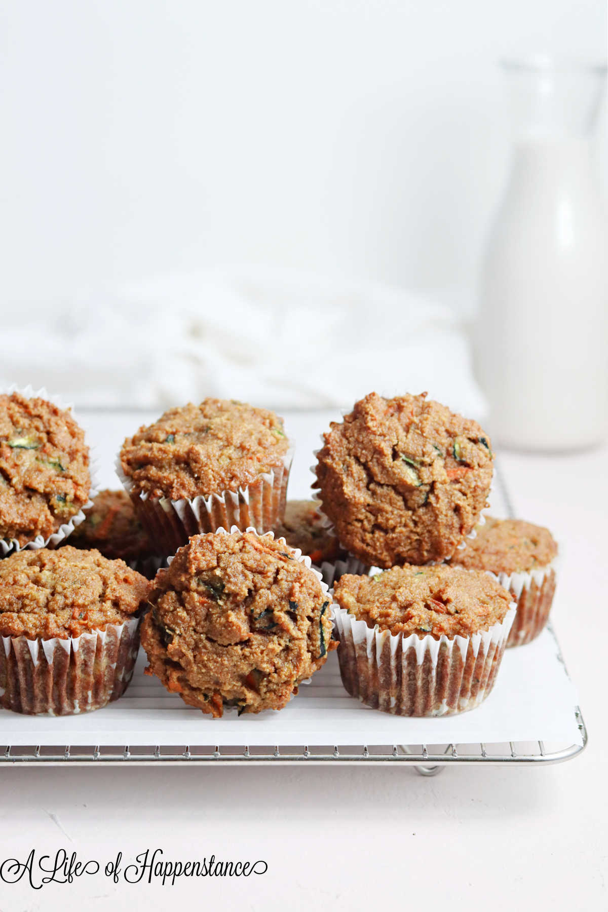 Muffins piled on a cooling rack with a white napkin and glass jar of cashew milk in the background.