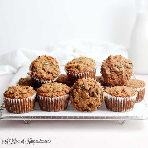 Healthy carrot zucchini muffins piled up on a cooling rack.