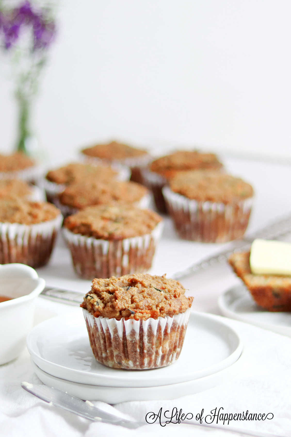 The healthy muffin on a small white plate with the remaining muffins in the background.