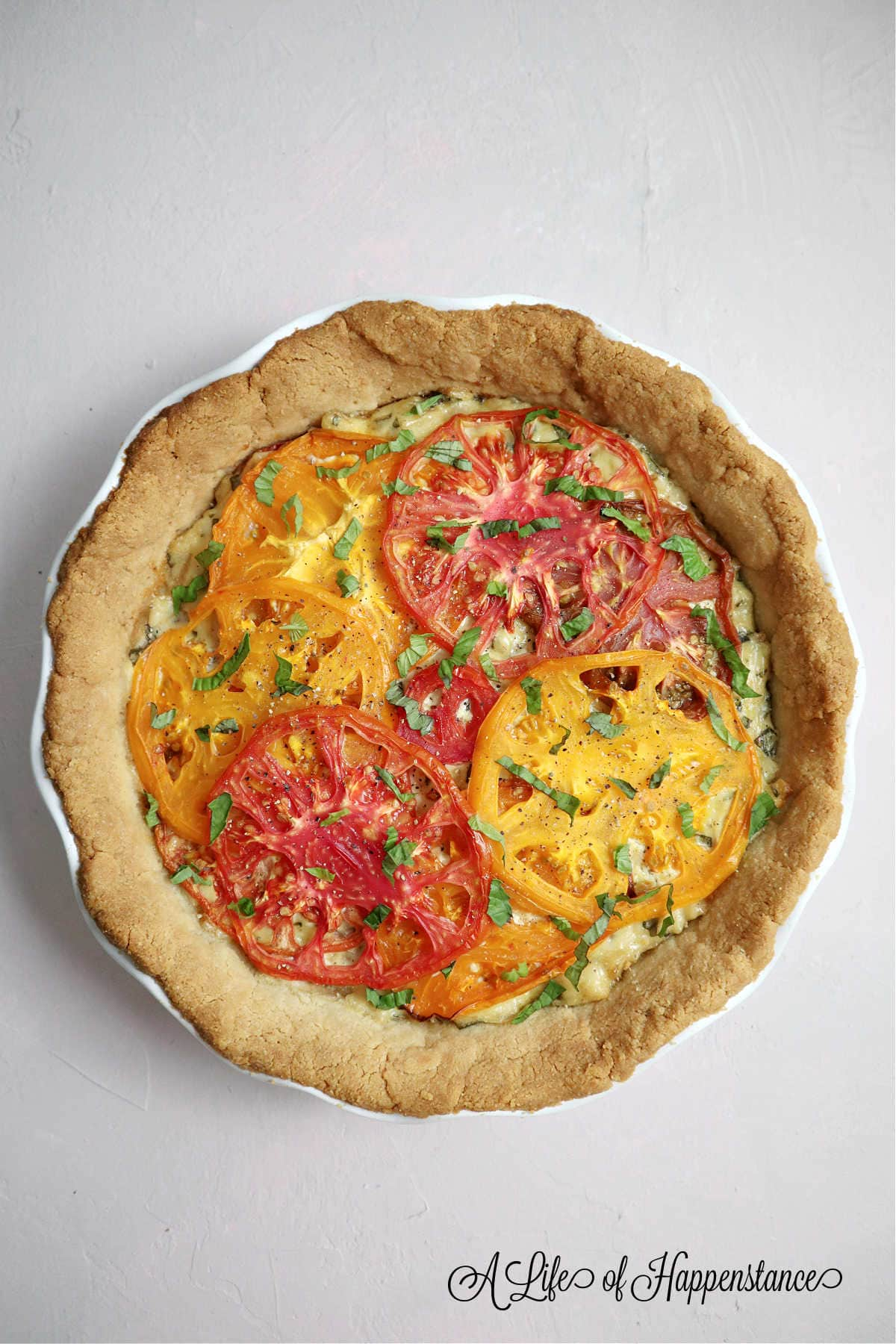 The cooked heirloom tomato pie on a light pink table.