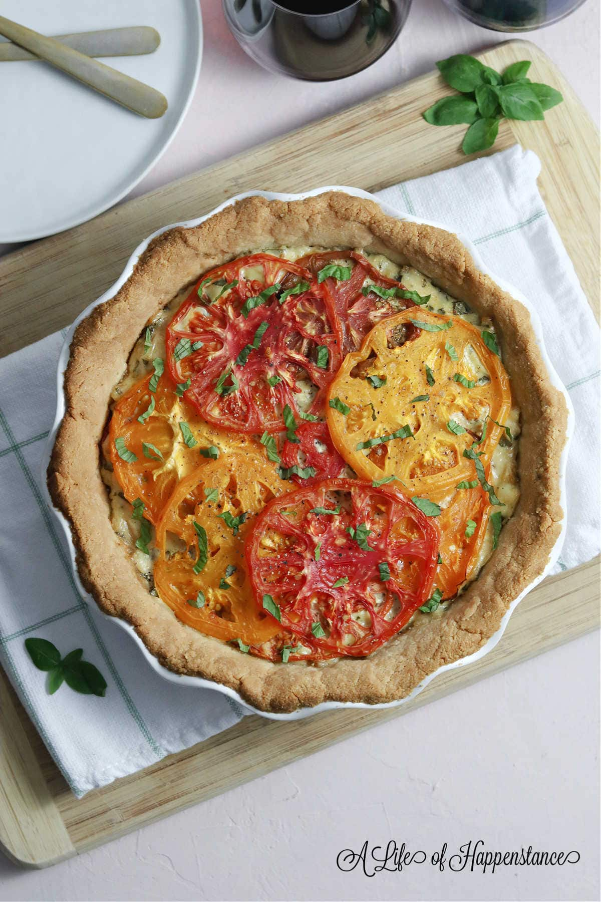 An overhead photo of the heirloom tomato pie recipe on a wooden cutting board surrounded by fresh basil leaves, two glasses of red wine, and a white plate.