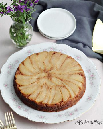 The upside-down paleo pear cake on a white plate surrounded by purple flowers, white plates, and a gray kitchen towel.