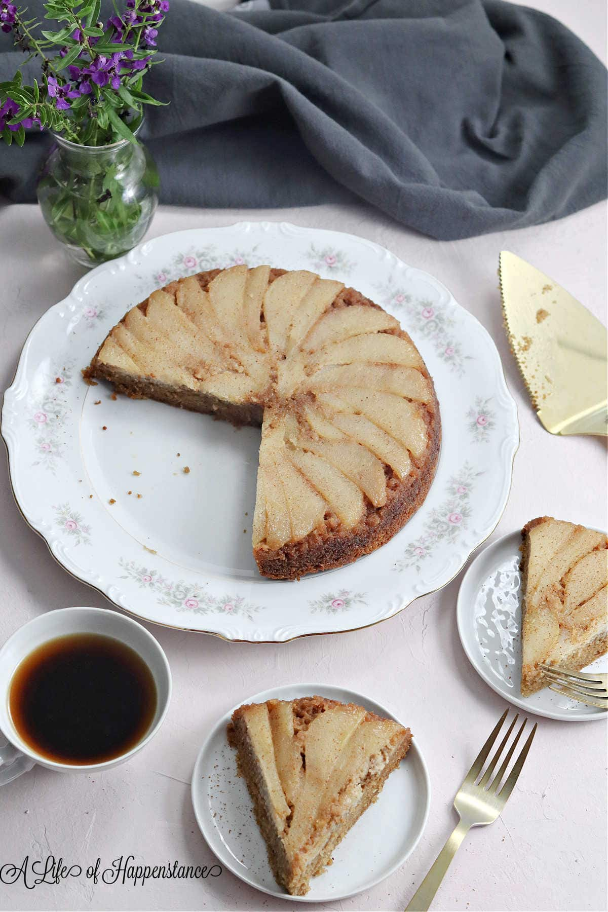 Slices of cake on white plates along with a cup of coffee and a gray kitchen towel.