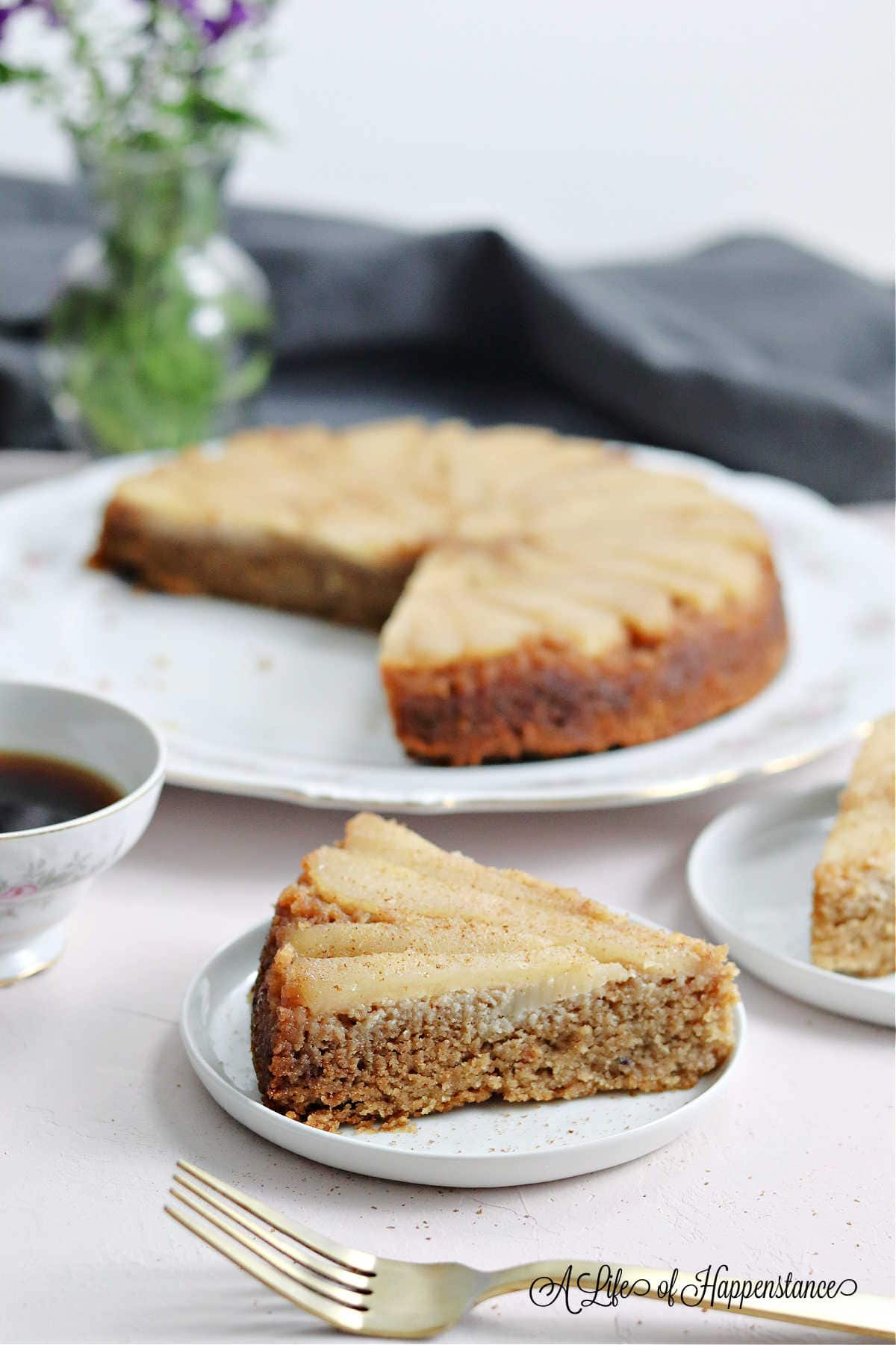 A slice of paleo pear cake on a white plate.