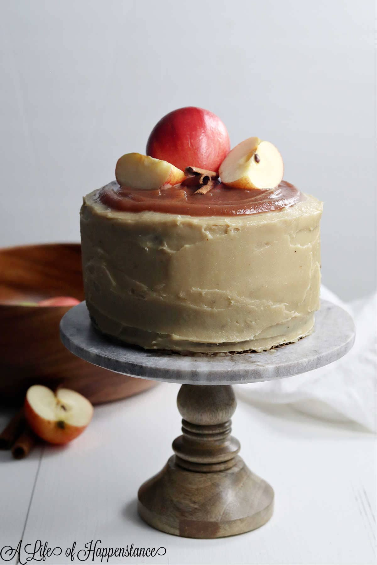 The apple cake on a cake stand with a wooden bowl filled with apples in the background.