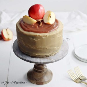 The apple cider layer cake on a cake stand with sliced apples and cinnamon sticks on top.